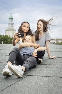 Germany, Berlin, three friends sitting  on roof top taking selfie with smartphone - OJF000164