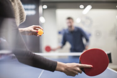 Two colleagues playing table tennis in office break room - ZEF009708