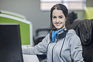 Portrait of smiling young wearing headphones in office - ZEF009726