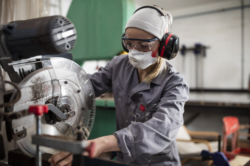 Woman wearing earmuffs and dust mask working on machine - ZEF009753