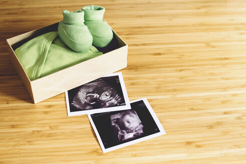 Baby girl ultrasounds, normal one and 4D, next to a gift box with tiny clothes and shoes on wood - GEMF000961