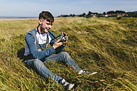 Smiling young man sitting on a meadow looking at camera - BOYF000533