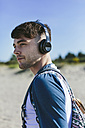 Young man with wireless headphones on the beach - BOYF000551