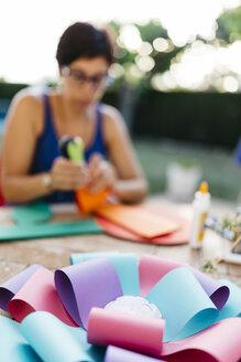Woman making a cardboard rosette - JRFF000837
