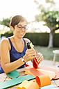 Woman doing handicrafts at garden table - JRFF000840