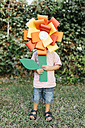 Boy holding home-made cardboard flower in front of his face - JRFF000849