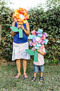 Mother and son holding home-made cardboard flowers in front of their faces - JRFF000852