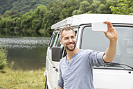 Smiling man taking a selfie at a van at lakeside - FMKF002798