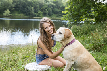 Young woman with her dog sitting at lakeside - FMKF002813