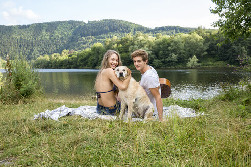 Young couple with dog sitting at lakeside - FMKF002816