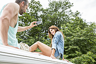 Couple sitting on roof of a van taking cell phone picture - FMKF002828