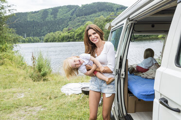 Happy mother with toddler at van at lakeside - FMKF002849