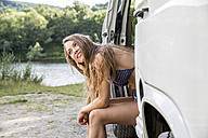 Young woman sitting in a van at lakeside - FMKF002864