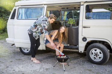 Young couple having a barbecue at a van - FMKF002867