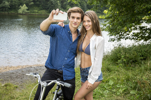 Young couple with bicycle at lakeside taking a selfie - FMKF002873