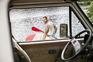 Man carrying stand up paddle board at lakeside behind van - FMKF002879
