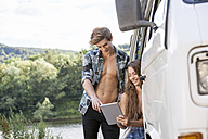 Young couple at a van at lakeside using digital tablet - FMKF002882