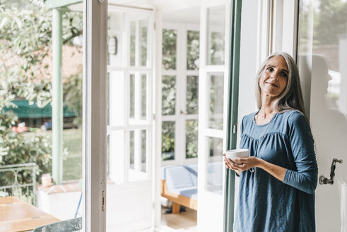 Smiling woman leaning at door frame of her winter garden with cup of coffee - KNSF000246