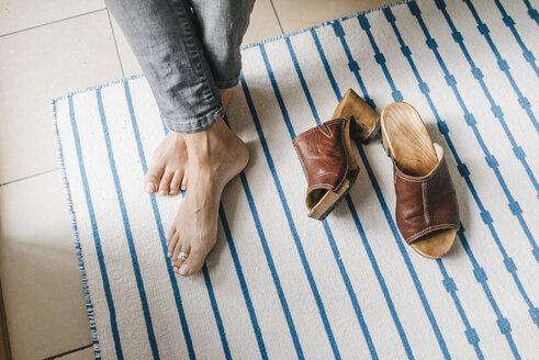 Barefoot feet of a woman beside her shoes - KNSF000249