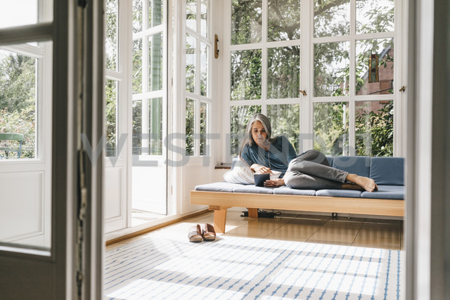 Woman lying on lounge in winter garden reading e-book - KNSF000252 - Kniel Synnatzschke/Westend61