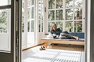 Woman lying on lounge in winter garden reading e-book - KNSF000252