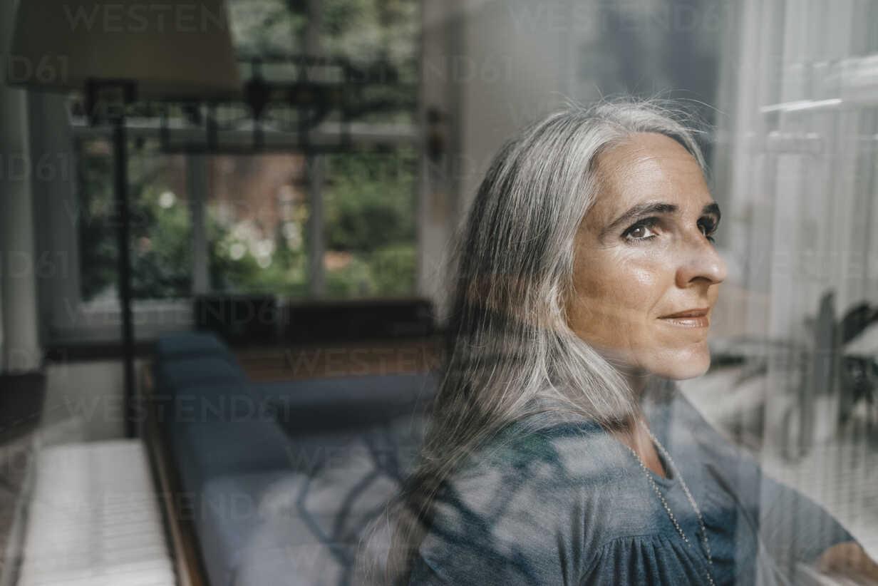 Woman at home looking through windowpane - KNSF000255 - Kniel Synnatzschke/Westend61