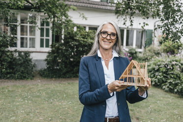 Smiling businesswoman with architectural model in the garden - KNSF000258