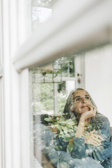 Smiling woman sitting behind windowpane looking at distance - KNSF000267