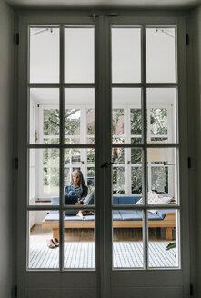 Woman sitting on lounge in winter garden using laptop - KNSF000270