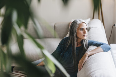 Pensive woman sitting on the couch looking through window - KNSF000273