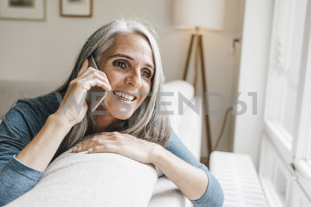 Smiling woman sitting on the couch telephoning with cell phone - KNSF000276 - Kniel Synnatzschke/Westend61