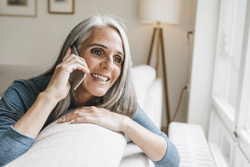 Smiling woman sitting on the couch telephoning with cell phone - KNSF000276