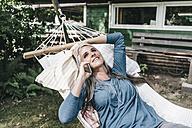 Woman on the phone lying in hammock in the garden - KNSF000279