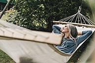 Woman relaxing in hammock in the garden - KNSF000288