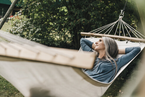 Woman relaxing in hammock in the garden - KNSF000288