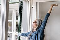 Smiling woman raising her arm - KNSF000291