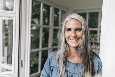Portrait of happy woman with long grey hair leaning against door case of her winter garden - KNSF000294