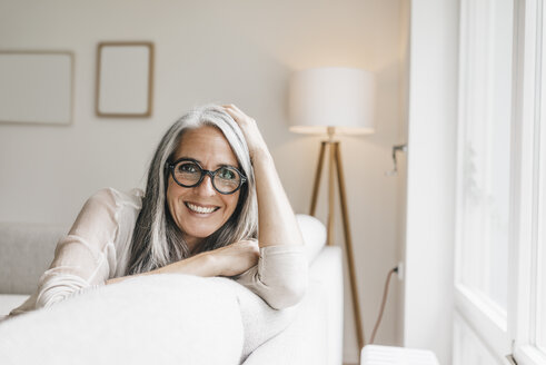 Portrait of smiling woman sitting on the couch at home - KNSF000300