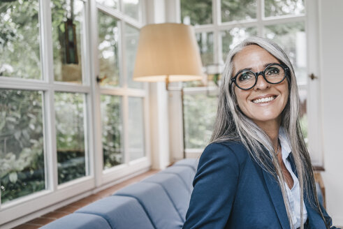 Portrait of smiling woman with spectacles in winter garden - KNSF000303