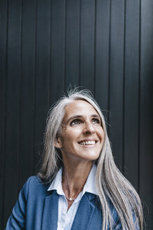 Portrait of smiling woman with long grey hair looking up - KNSF000306