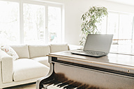 Laptop standing on piano in a living room - KNSF000321
