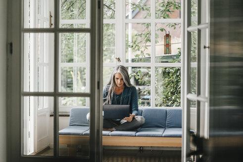 Woman sitting on lounge in winter garden using laptop - KNSF000324