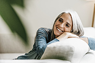 Smiling woman on the couch at home - KNSF000330