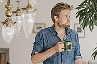 Pensive man with coffee mug at home - KNSF000342