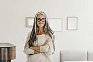Portrait of smiling woman with long grey hair and spectacles at home - KNSF000345