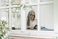 Woman sitting in winter garden reading e-book - KNSF000351