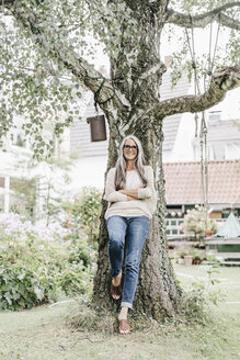 Smiling woman with long grey hair leaning against tree in the garden - KNSF000357