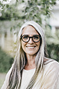 Portrait of smiling woman with long grey hair wearing spectacles - KNSF000360
