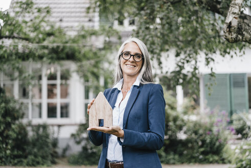 Portrait of smiling businesswoman with piece of wood shaped like a house standing in the garden - KNSF000363