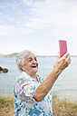 Happy senior woman taking selfie on the beach - RAEF001418
